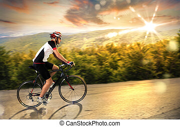 Cyclist at sunset - Man pedaling on an uphill road at sunset