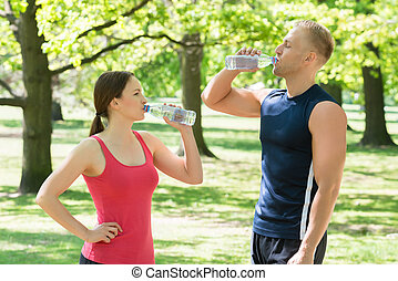 Couple Drinking Water In Park - Young Athletic Couple...