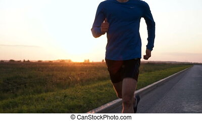 The athlete jogs at sunset.