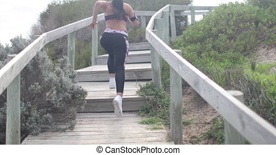 Young fit sports woman jogging on steps. Super slow motion...