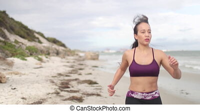 Young fit sports woman jogging on the beach. 4k slow motion...
