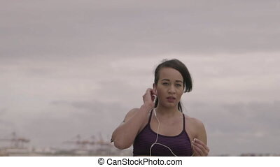 Young woman preparing for jogging on the beach at cloudy weather. Fitness. Slow Motion