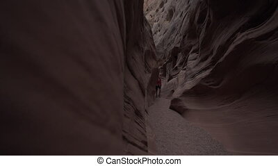 Utah Canyoneering - Young Woman Hiker exploring slot Canyon...