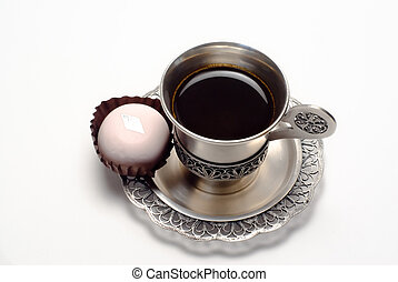 Silver cup of coffee with white cake