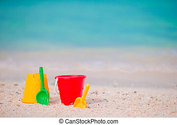 Kid's beach toys on white sand. Buckets and blades for kids...