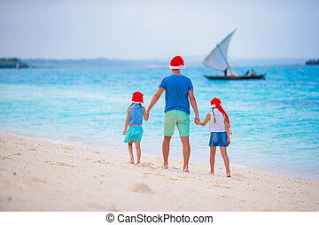 Happy family in Santa Hats on summer vacation Christmas...
