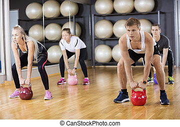 Determined Friends Lifting Kettlebells In Gym - Full length...