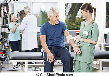 Nurse Putting Crepe Bandage On Senior Mans Hand - Smiling...