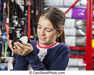 Happy Girl Holding Small Guinea Pig In Store - Happy cute...