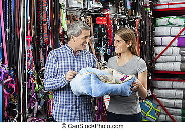 Smiling Couple Holding Pet Bed At Store - Smiling couple...