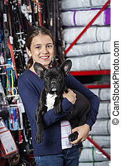Happy Girl Carrying French Bulldog In Store - Portrait of...