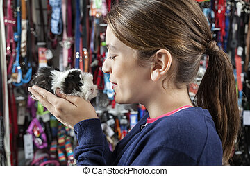 Cute Girl Holding Small Guinea Pig At Store - Side view of...