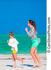 Little girl and young mother during beach vacation Happy...