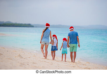 Happy family with two kids in Santa Hats on summer vacation...