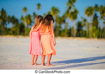 Little caucasian girls at beach during summer vacation Happy...