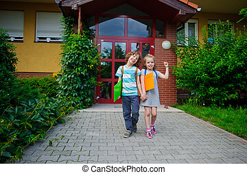 Boy and girl go on a schoolyard having joined hands.