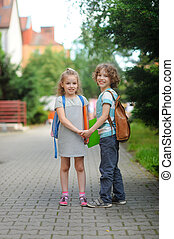 Two pupils, boy and girl, on the way to school. - Two pupils...