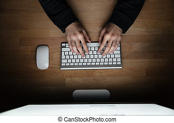 Hands of young man typing on keyboard