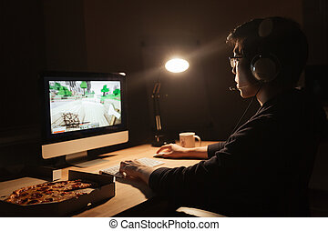 Gamer playing computer game and eating pizza in dark room -...
