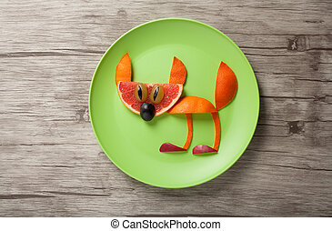 Funny cat made of orange on plate and desk