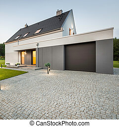 External view of stylish house with big garage and stone...