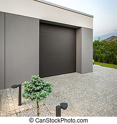 Modern home garage with stone driveway and decorative lights