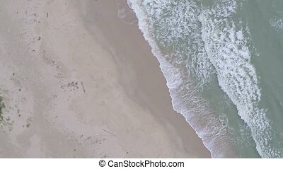 Sea tide and sandy beach. View from above, aerial slow...