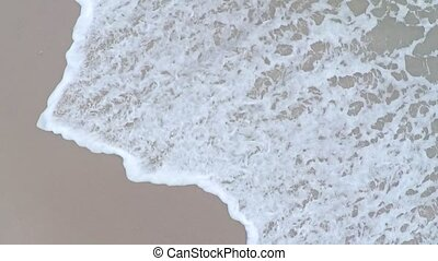 Aerial slow motion video of sea tide on a sandy beach