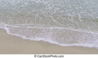 Surf on sandy beach with footprints Slow motion aerial video...