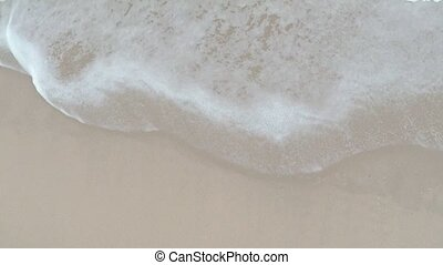Sea waves washing sandy shore. Aerial camera, slow motion video