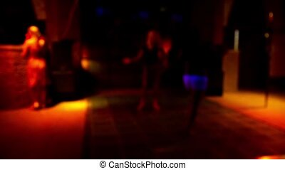 Dance floor in a disco club with young women dancing with defocused background