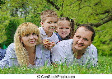 Happy family with two children lying on grass
