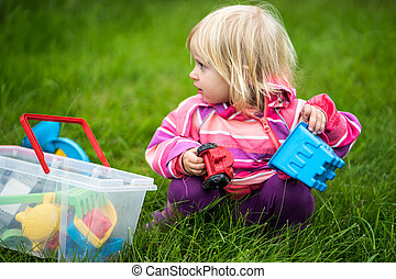 Little girl playing with her toys in the garden