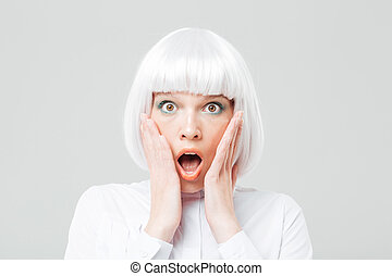 Scared shocked woman with opened mouth and hands on cheeks -...