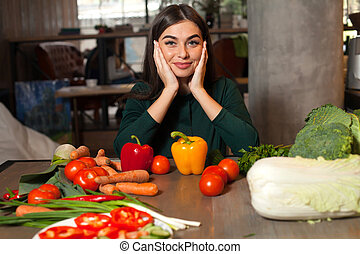 Smilling woman and vegetables - At the table with lots of...