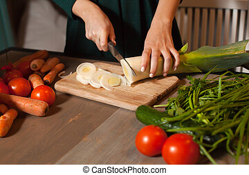 By woman is cuted onion - Close-up an onion is cuted by...