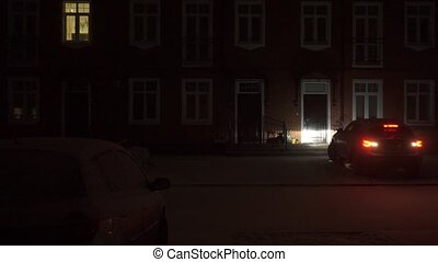 Big car drives away from a red brick townhouse at night clip