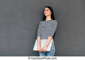 Lost in thoughts. Thoughtful young woman carrying laptop and looking away while standing against grey background