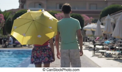 Young man and girl go hand in hand, along the pool. - Young...