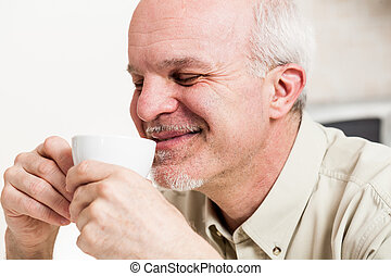 Grinning man sipping from tea cup - Close up on single...