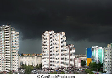 City storm - Urban landscape with black stormy clouds in th...