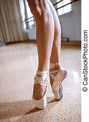 The close-up feet of young ballerina in pointe shoes against...