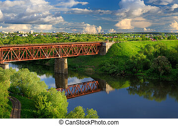 Railway bridge across small river in sunny summer day