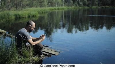 A man sits on a pier of the lake and taking pictures on the...