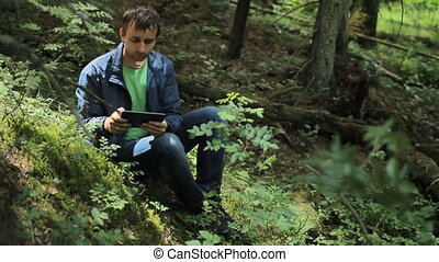 The man in the forest touch tablet. It sits on a small cliff green
