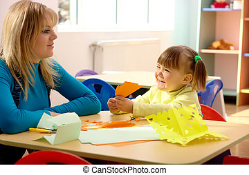 Teacher and little girl play with color paper