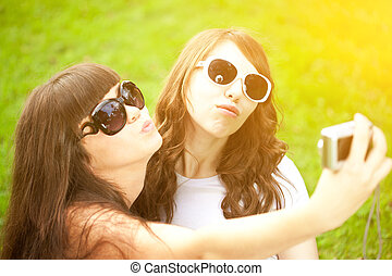 Duckface. Selfie. Two young trendy girls doing selfie. A...