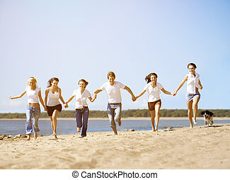 Group young friends enjoying a beach party on vacation....