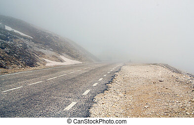fog-shrouded mountain road in the alps