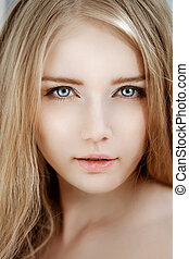 Woman face close up. A pretty young blond trendy. Girl with...